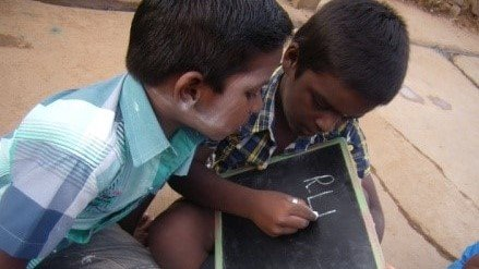 Two boys practice their spelling on a small chalkboard