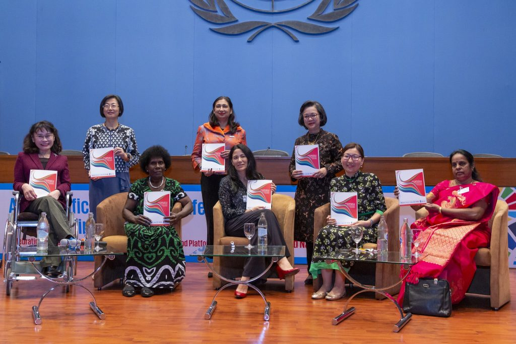 Eight women sit on a stage holding certificates presented by the UN-ESCAP