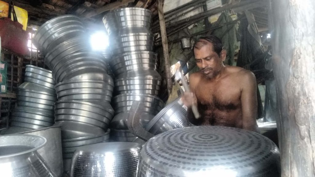 A man hammers a large bowl, he is surrounded by stacks of large metal bowls.