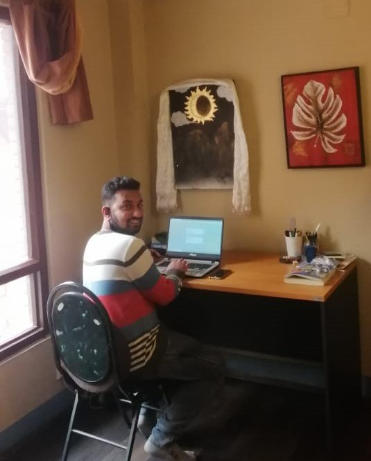 Yubraj contacting workers from his office in Nepal